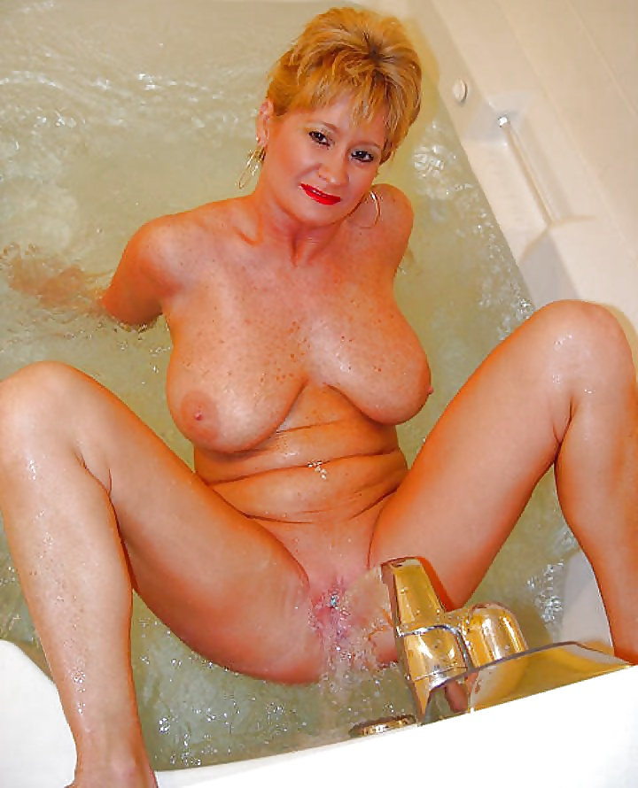 Mature woman spreads her hairy pussy wide open and masturbates in the bathtub