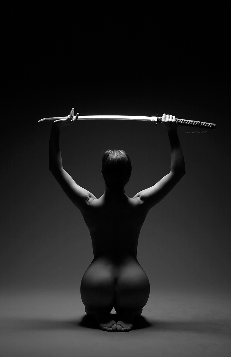 Nude babe posing with a big sword
