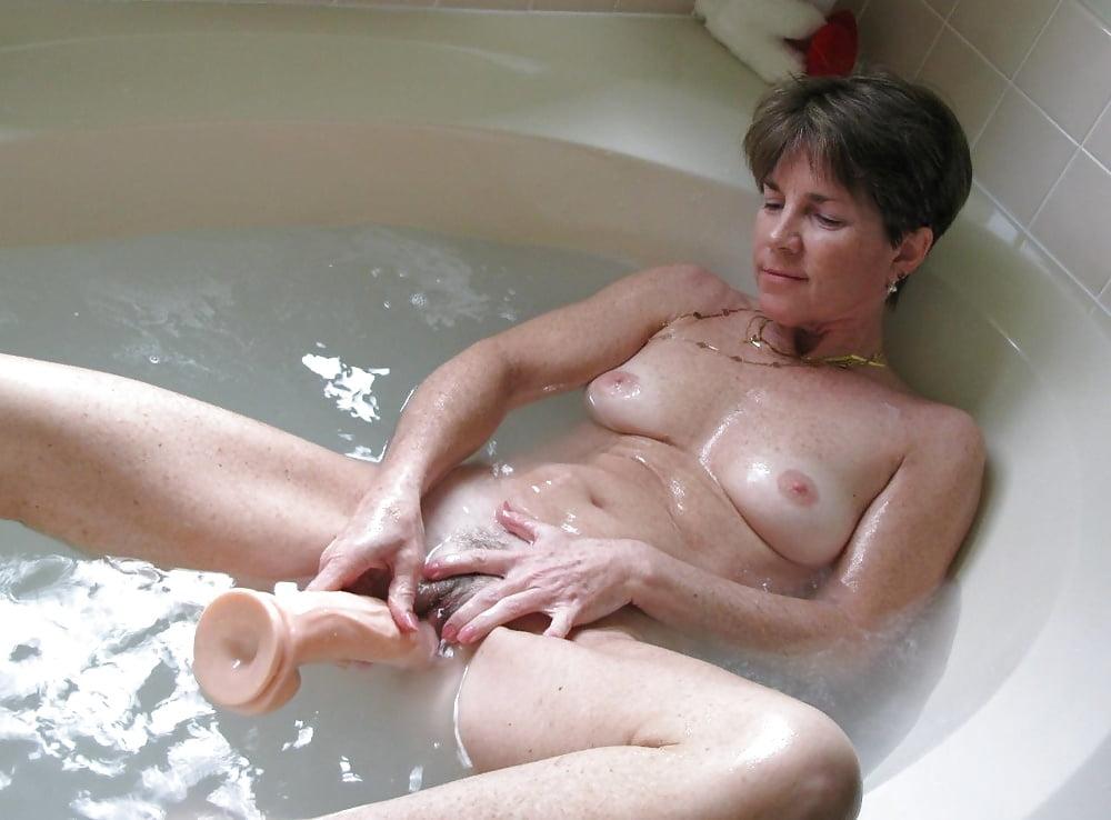 Hot mature woman slips off lingerie before masturbating in the bathtub